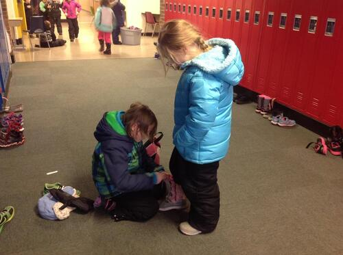 Student assisting another student with her boots.