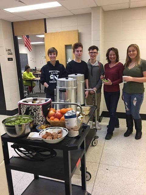 Picture of 4 students with the coffee cart that is shared with teachers
